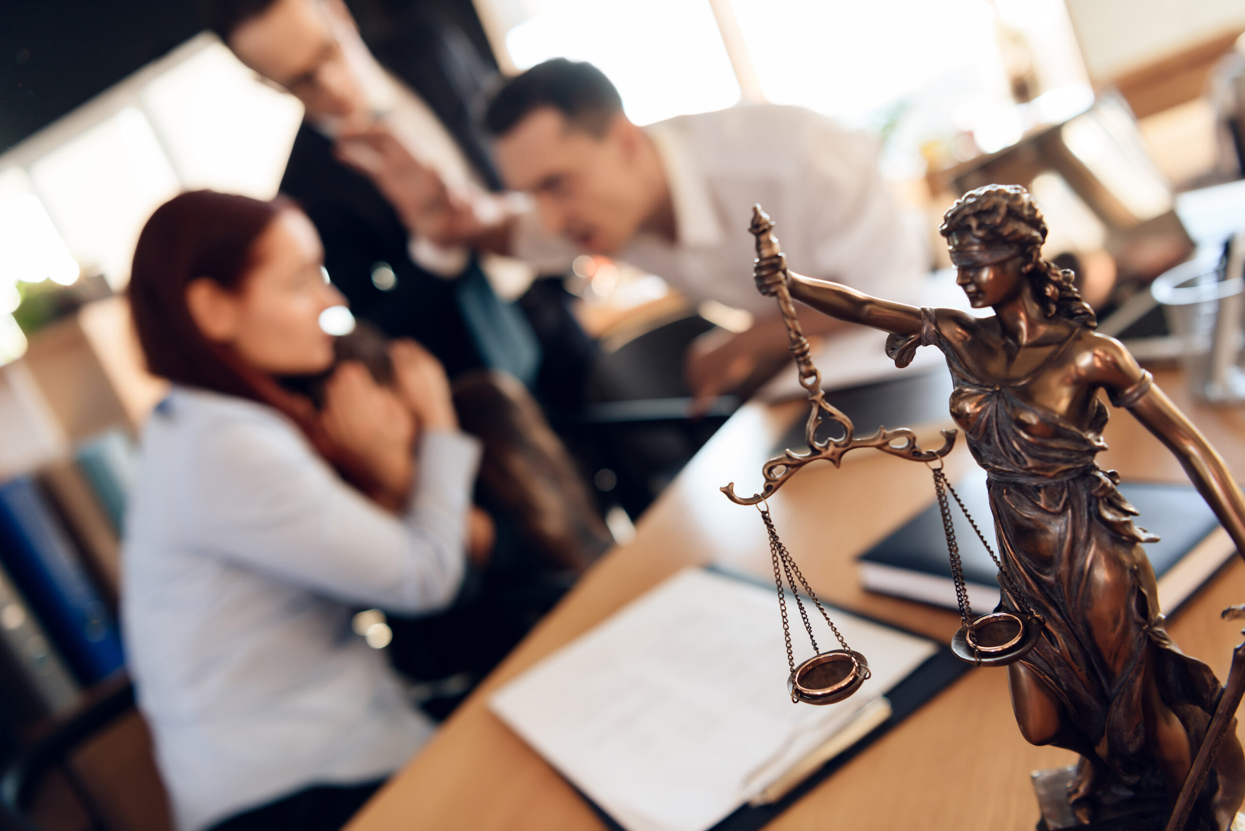 Bronze figurine of Themis holds wedding rings on scales of balance, being in foreground. Couple divorce. Adult couple gets divorced from attorney for divorce in office.
